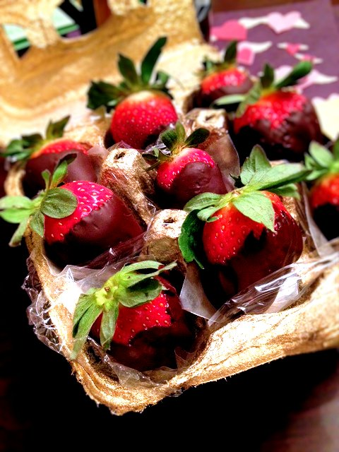 Gold spray painted egg carton lined with saran and holding homemade chocolate covered strawberries.